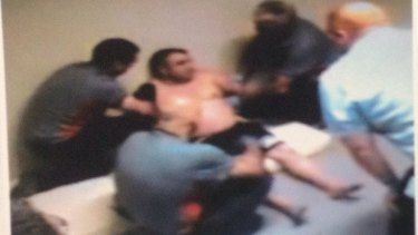 CCTV from December 2015 shows security guards restraining a detainee at the Maribyrnong centre.