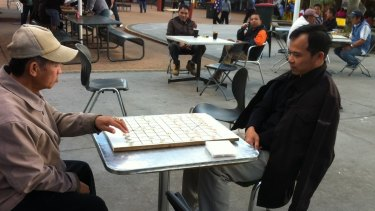 Men playing checkers at Inala Plaza.