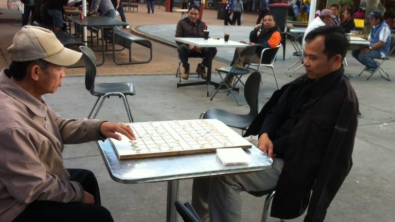 Men playing checkers at Inala Plaza.