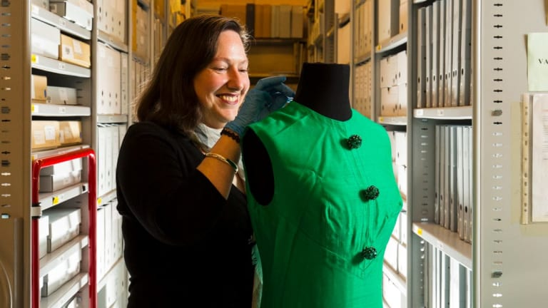 Carolyn Laffan, senior curator at the Australian Music Vault with a dress worn by Judith Durham of The Seekers at the Sidney Myer Music Bowl, 1967.