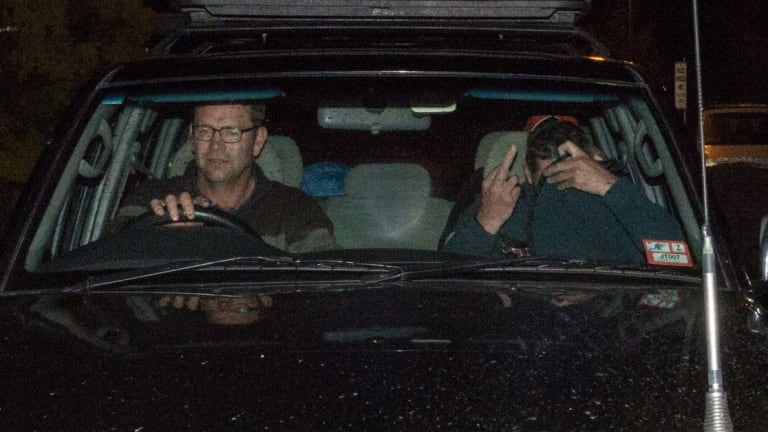 Mark Tromp, pictured right, is driven from the Wangaratta police station on Saturday night.