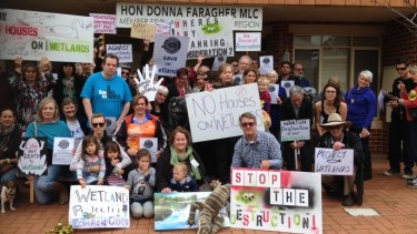 Protesters gather outside Planning Minister Donna Faragher's office.