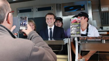 French centrist candidate Emmanuel Macron poses with employees at a fast-food restaurant.