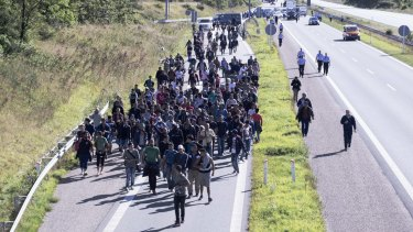 Hundreds of refugees are escorted by Danish police on a highway in southern Denmark.