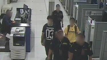 The teens are escorted at Sydney Airport by Customs officials.