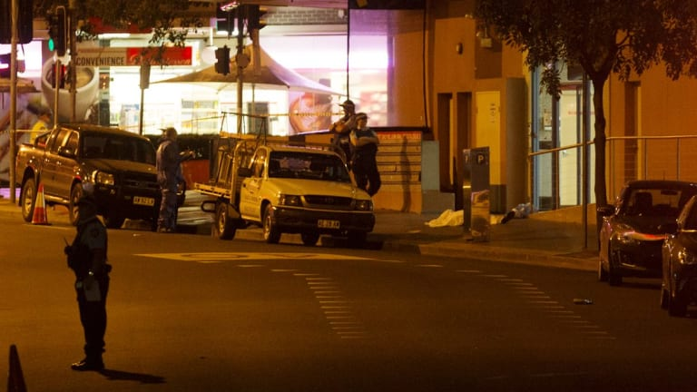 A body lies on the ground after the shooting outside the NSW Police Headquarters.