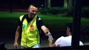 Take Kare co-ordinator Nate Brown offers a bottle of water to a late-night reveller.