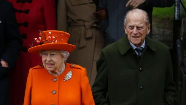 Britain's Queen Elizabeth II and Prince Philip, right, wait for their car following the traditional Christmas Day church service, at St. Mary Magdalene Church in Sandringham, England, Monday, Dec. 25, 2017. (AP Photo/Alastair Grant)