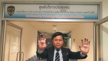 Pravit Rojanaphruk showing his ink-stained hands after being fingerprinted by police.