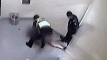 Video still allegedly shows a police officer standing on a woman's legs while she is held in custody in Ballarat