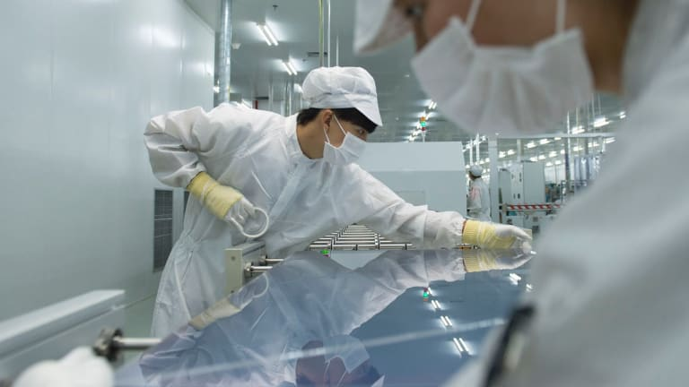 Chinese workers manufacture solar panels at the plant of Zhejiang Changxing Hanergy Solar PV in Huzhou