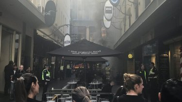 Smoke fills Degraves Street in the city after the cafe fire.