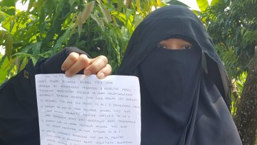 Michael Titus Igweh's sister-in-law Nila holds up a family statement condemning the execution.