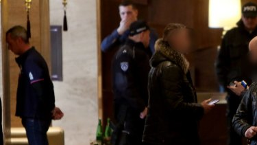 Rohan Arnold, on left, is detained in the lobby of a Belgrade hotel.