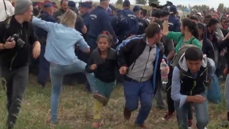 Hungarian camerawoman Petra Laszlo, centre left in blue, kicks out at a young migrant in Hungary on September 8.