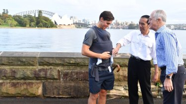 President Joko Widodo and Prime Minister Malcolm Turnbull talk to a father carrying his eight-week-old baby.
