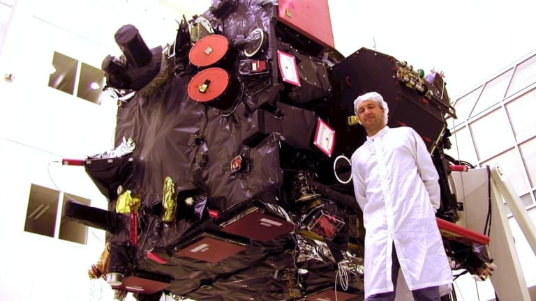 Former Canberra student and engineer Warwick Holmes with the Rosetta spacecraft, which has travelled more than 8 billion kilometres since he helped launch it in 2004.