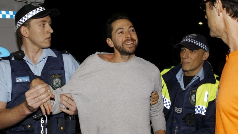 James Mathison is led away by police after trying to scale one of the Moreton Bay Fig trees on Anzac Parade, Moore Park, at a protest before they are cut down tonight in Sydney.