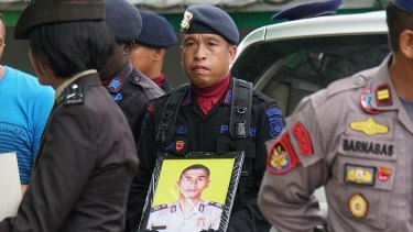 An officer holding Brigadier Firman's photo at his funeral.