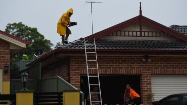 A man removes damaged tiles from the roof of a home on Methven Street in Mount Druitt.