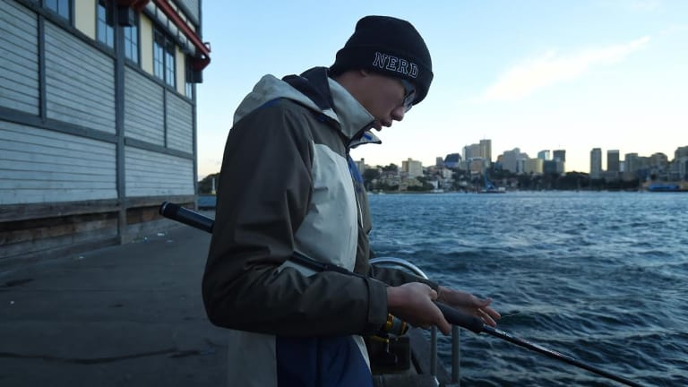 Eddie Yin, 24, tries to keep warm while fishing at Walsh Bay in Sydney on Wednesday morning.