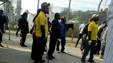 Papua New Guinea police entering the Manus Island immigration detention centre.