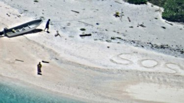 An 'SOS' message in the sand saved two men stranded on a remote island.