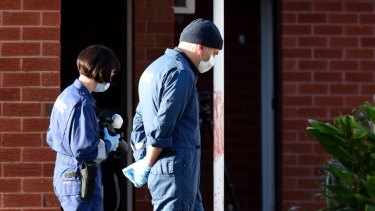 Forensics police walk past blood found on a pole outside units in St Albans.