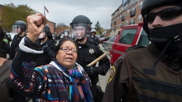 Faenette Black Bear, 63, Lakota, raises her fist in defiance as riot police push peaceful protesters away from the Morton County Court House.