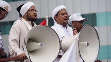 Rizieq Shihab (with microphone) speaks at a protest in January. He has now been named as a suspect by police.