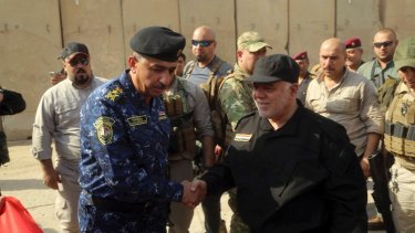 Iraqi Prime Minister Haider al-Abadi, right, shakes hands with Lieutenant-General Raid Shaker Jawlat upon his arrival in Mosul on Sunday.