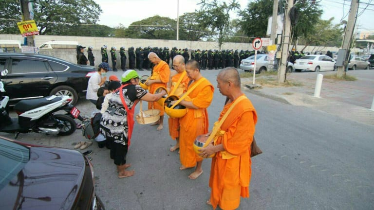 Monks at Thailand's largest Buddhist temple Wat Dhammakaya accept an offering while police line up in the background.