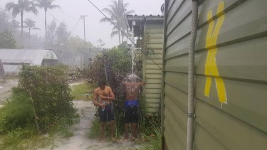 Men inside the now-closed regional processing centre at Manus Island,  showering in the rain.