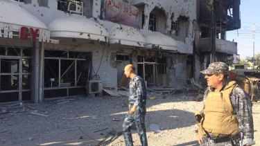 Iraqi security forces inspect one of the damaged buildings after clashes between Iraqi security forces and members of the Islamic state in the city of Kirkuk on October 22.