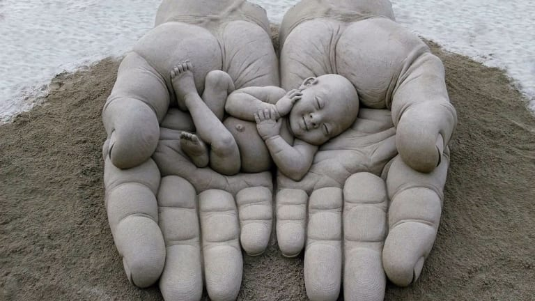Hands holding a baby, sand sculptor by Dennis Massoud in the Canary Islands.
