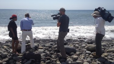 Reporters shown the spot where a small piece of metal was found on a beach in Saint-Denis, Reunion Island. Police have take the object away.