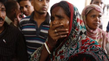 A relative of a fire victim cries as victims' bodies are carried into a makeshift morgue at a hospital after the fire broke out.