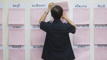 A voter checks a registration board at a polling station in Bangkok.