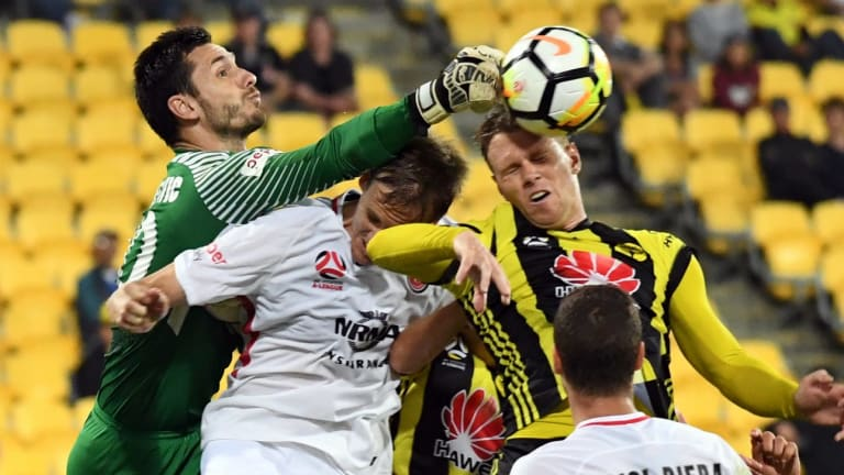 Congestion: Vedran Janjetovic of the Wanderers punches the ball away during a frantic finish at Westpac Stadium.