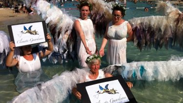 The Climate Guardians sink into the South Bank Parklands lagoon to represent rising ocean levels.