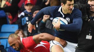 Tim Visser of Scotland bursts through a tackle.