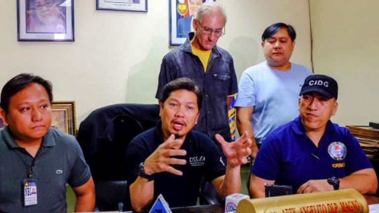 Calls for reintroduction of death penalty in the Philippines: Alleged Australian sex offender Peter Gerard Scully stands behind Philippines police investigator Angelito Magno.