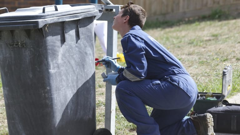 A forensics police officer dusts a bin near where a 17-year-old Canterbury Girls' Secondary College student was stabbed to death.