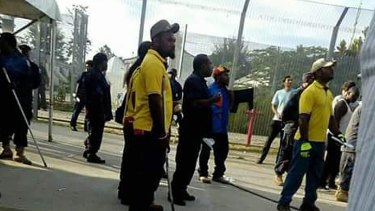 Papua New Guinea police officers enter the Manus Island immigration detention centre.