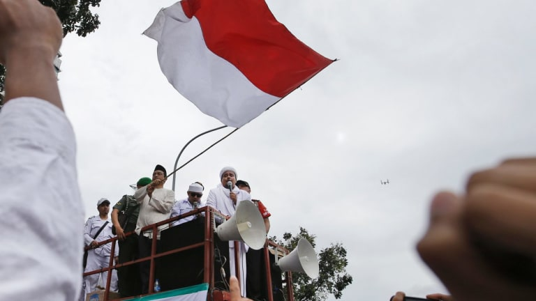 Muslim protesters raise their fists as the leader of Islamic Defenders Front, Rizieq Shihab, gives a speech during a protest against Ahok in October.