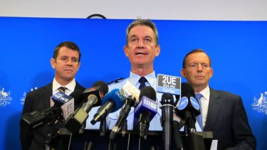 NSW Police Commissioner Andrew Scipione (centre), flanked by NSW Premier Mike Baird and Prime Minister Tony Abbott, has been criticised for failing to resolve the scandal.