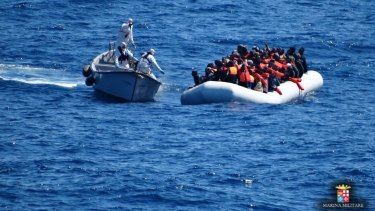 Italian navy personnel, left, approach a rubber dinghy filled with migrants in the Sicilian Channel on Friday.