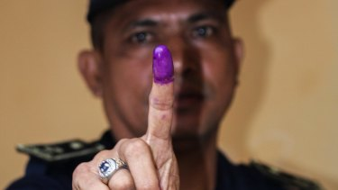 A National Police officer shows his finger after voting in Farol, Dili, on Monday.