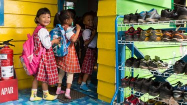 Children remove their shoes before they enter the classroom at Global Andalan school in Riau province. As part of the Fire-Free Villages program, APRIL is starting to reach out to school children.