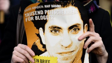 An Amnesty International activist holds a picture of Saudi blogger Raif Badawi at a protest in Germany in January.
